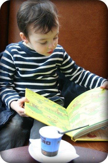 boy reading while he drinks babycino