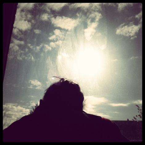 boy looking out window in morning sunshine