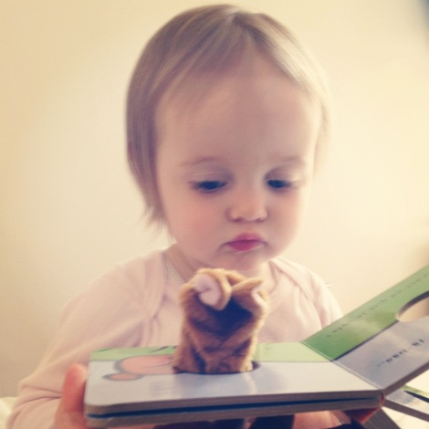 girl looking unsure at pop-up rabbit in book