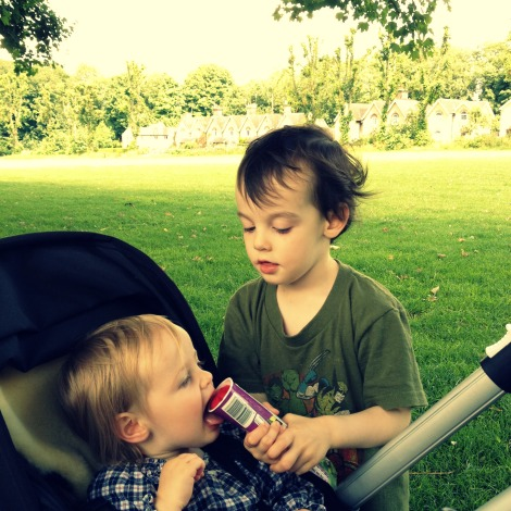 boy sharing ice lolly with his sister