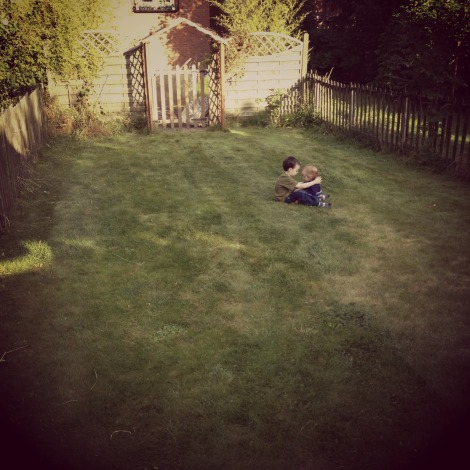 brother and sister hug in the garden