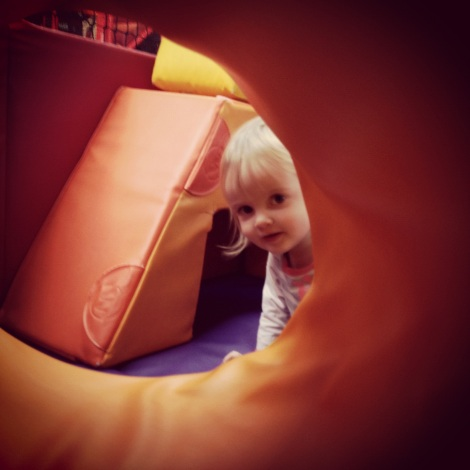 girl at soft play looking through the tunnel