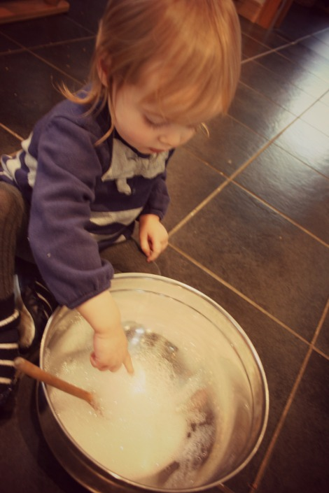 toddler cuatiously putting a finger in a bowl of bubbles
