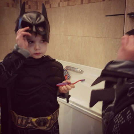 child in Batman costume scowling