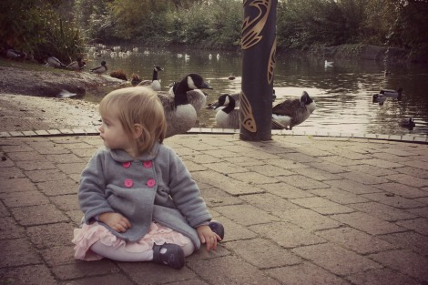 girl sitting watching ducks