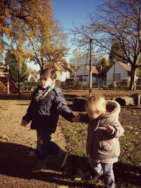 brother and sister hold hands in the park