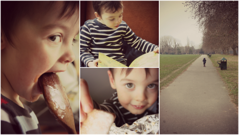 three year old boy licking wooden spoon, reading book, scooting in the park