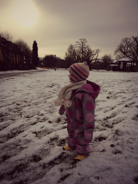 Toddler standing in snow in park