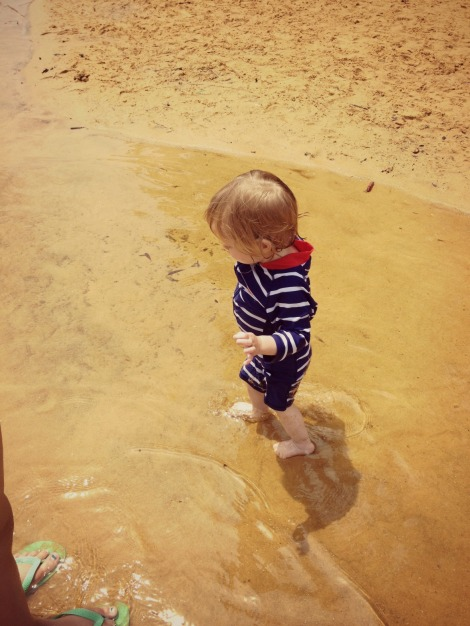 Toddler playing in water on beach