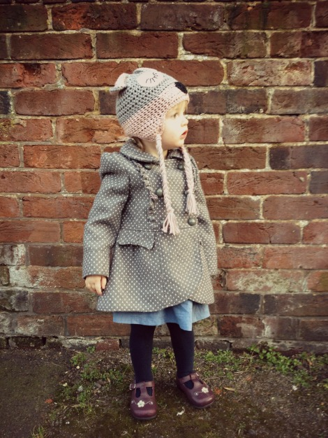 toddler standing against brick wall