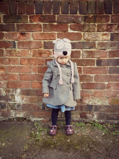 toddler against brick wall