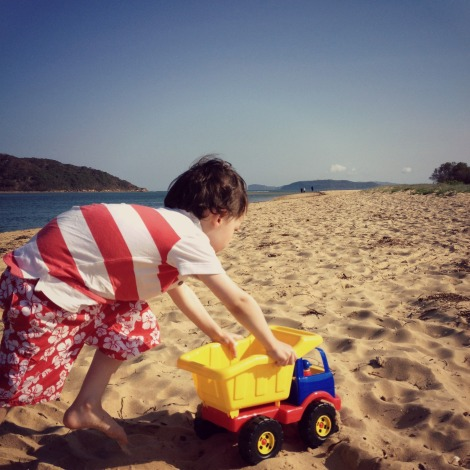 boy playing on beach with dump truck