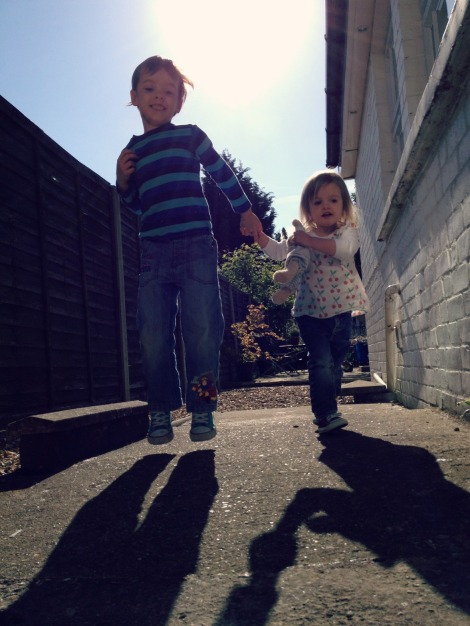 brother and sister jump in morning sun