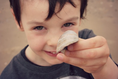 boy holding shell out