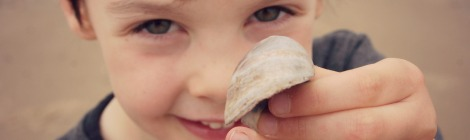 smiling boy holding shell