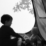 Boy sitting in a tent playing with a teddy