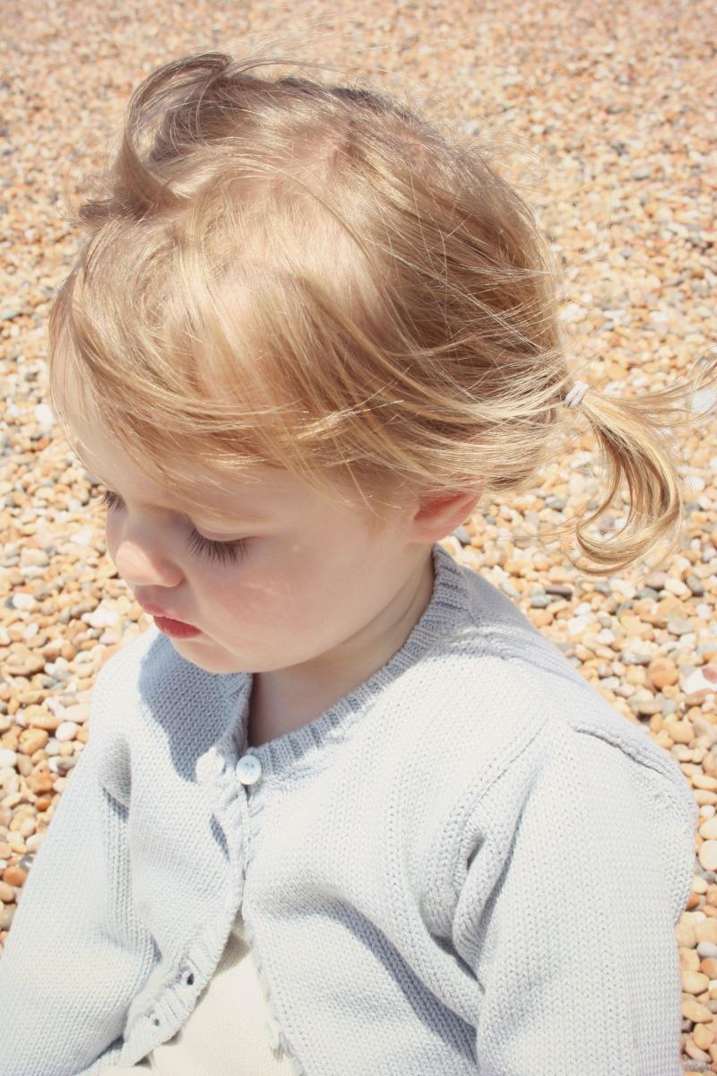 girl in blue cardigan on beach