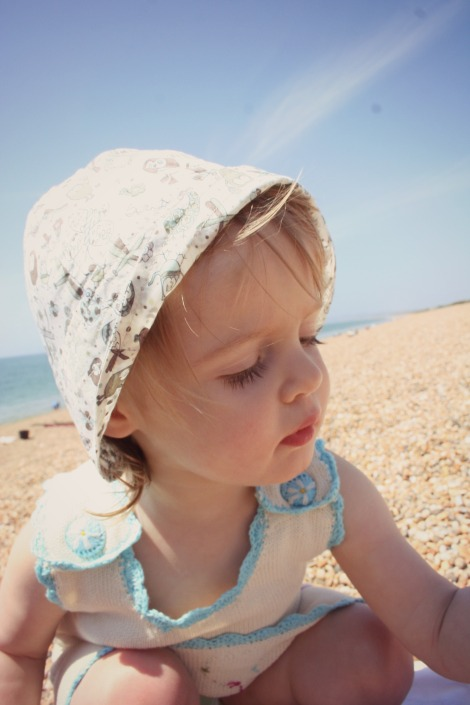 girl in print sunhat and knit dress on beach
