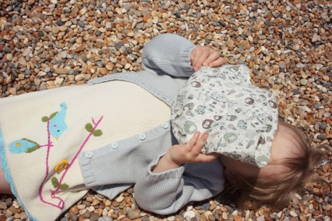 girl in cardi and knit dress laying on beach