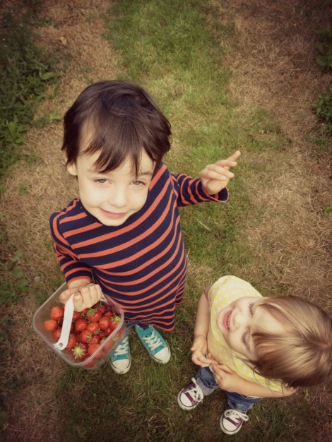boy and girl with punnet of strawberries