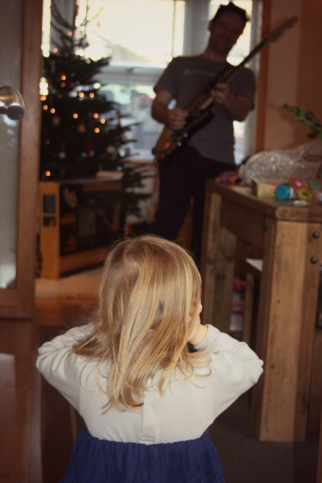 girl covering ears as father plays guitar